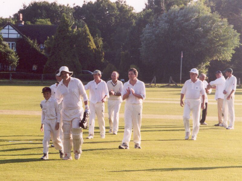 The end of another sunny Saturday afternoon's cricket in idyllic surroundings. Badgers leave the field after defeating Ewhurst, July 2000